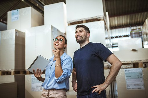 woman and man taking inventory in warehouse