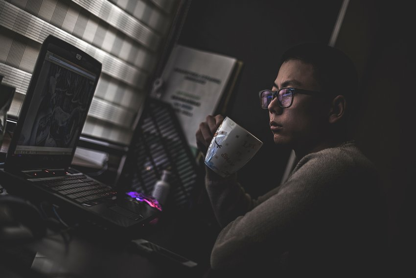 Side view of Asian man working remote from his laptop in a darkly lit room