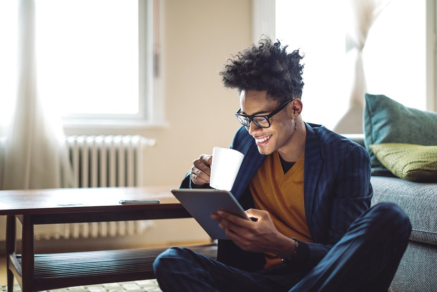 Man sitting on floor working remote enjoying coffee and on his smart device